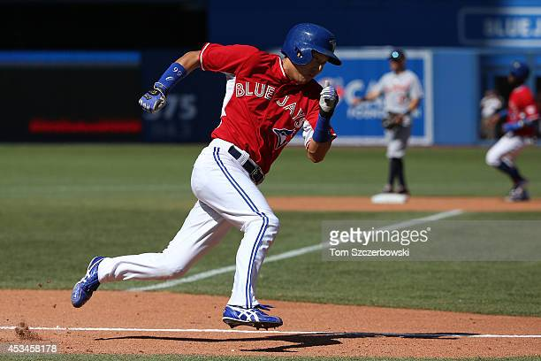 Munenori Kawasaki of the Toronto Blue Jays runs around third base and towards home plate to score a run in the seventh inning during MLB game action...