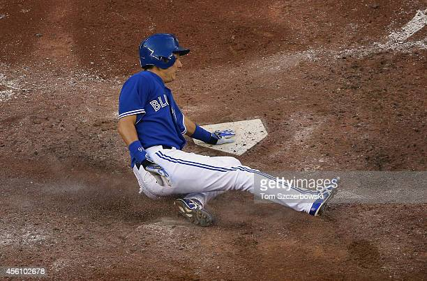 Munenori Kawasaki of the Toronto Blue Jays slides across home plate to score a run in the fifth inning during MLB game action against the Seattle...