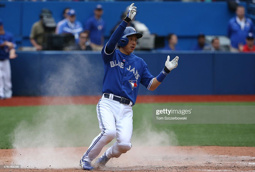 Munenori Kawasaki #66 of the Toronto Blue Jays slides across home plate to score a run on an RBI single by Jose Reyes #7 in the ninth inning during MLB game action against the Houston Astros on June 7, 2015 at Rogers Centre in Toronto, Ontario, Canada.