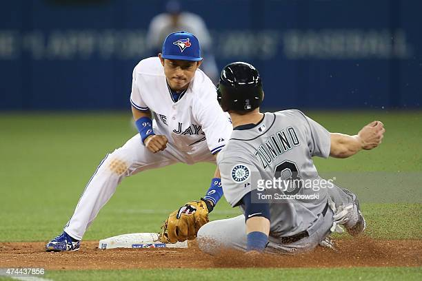 Munenori Kawasaki of the Toronto Blue Jays tags out Mike Zunino of the Seattle Mariners as he is caught stealing second base in the ninth inning...