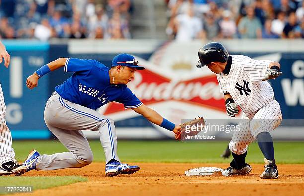 Munenori Kawasaki of the Toronto Blue Jays tries to tag out Ichiro Suzuki of the New York Yankees at second base in the fifth inning at Yankee...