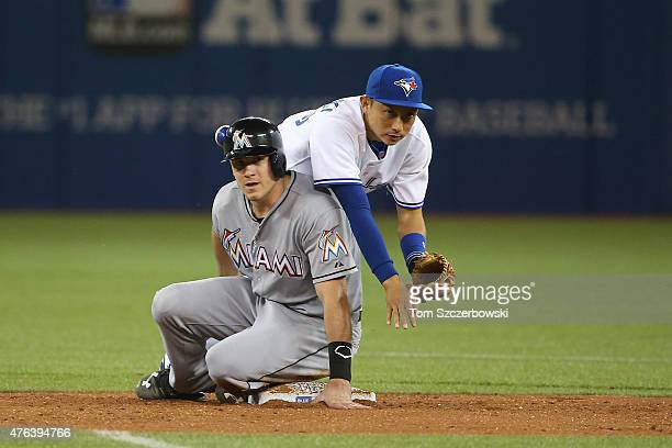 Munenori Kawasaki of the Toronto Blue Jays turns a double play in the seventh inning during MLB game action as JT Realmuto of the Miami Marlins...