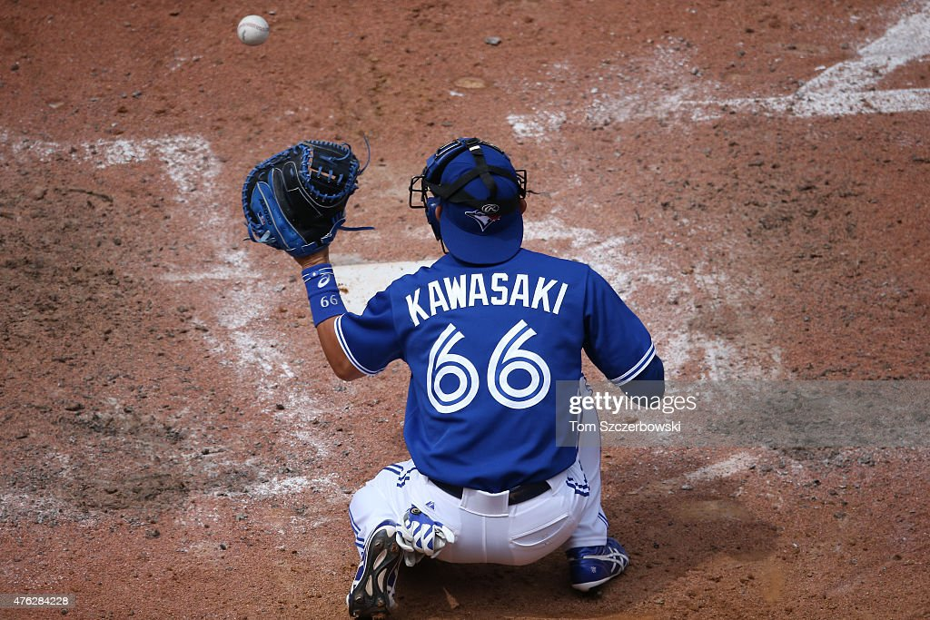 Munenori Kawasaki #66 of the Toronto Blue Jays warms up the pitcher as he catches before the start of the seventh inning during MLB game action against the Houston Astros on June 7, 2015 at Rogers Centre in Toronto, Ontario, Canada.