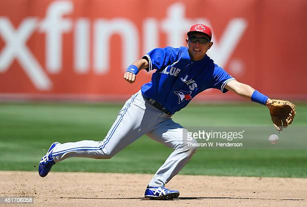Munenori Kawasaki of the Toronto Blue Jays watches the ball get past his glove for a basehit off the bat of Coco Crisp of the Oakland Athletics in...