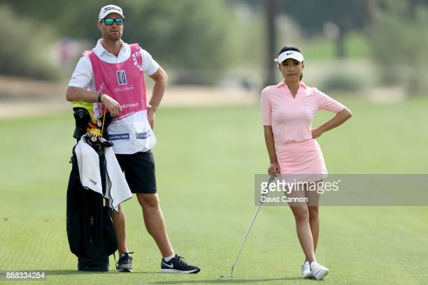 Muni He of China waits to play her second shot on the par 4 12th hole with her caddie Stephen Deane during the third round of the 2017 Dubai Ladies...