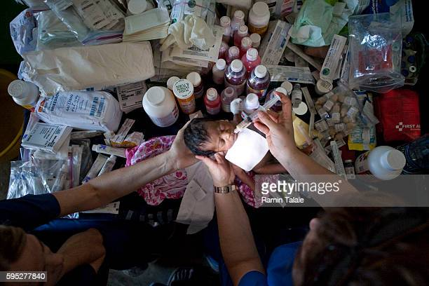 Muni Tahzib , a doctor from Hoboken, NJ, and Maryanne Fike, a volunteer also from Hoboken, NJ, examine a newly born baby at a makeshift clinic in the...