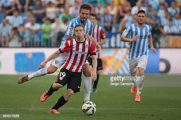 Muniain of Athletic Club Bilbao is tackled by Ignacio Camacho of Malaga CF during the La Liga match between Malaga CF and Athletic Club Bilbao at La...