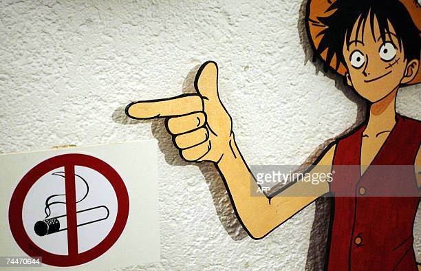 A cardboard comic figure points to a nosmoking sign during a comic festival in the southern German city of Munich 08 June 2007 The smoking issue is...