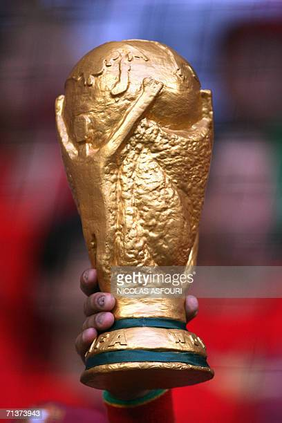 A fan holds up a replica of the World Cup trophy before the start of the semifinal World Cup football match between Portugal and France at Munich's...