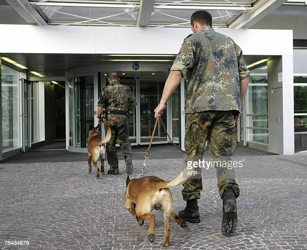 Soldier of the Federal Armed Forces Bundeswehr and his sniffer dog enter a military hospital in Ulm, southern Germany, after German authorities...