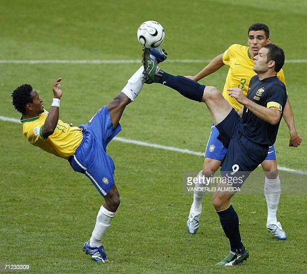 Brazilian midfielder Ze Roberto and Australian forward Mark Viduka fight for the ball as Brazilian defender Lucio looks on in their opening round...