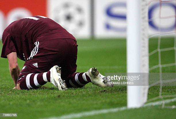 FC Bayern Munich's striker Lukas Podolski kneels on the pitch after a missed chance against AC Milan during their Champions League quarterfinal...