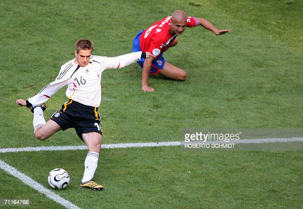 German defender Philipp Lahm shoots to score as Costa Rican defender Luis Marin looks on during their opening match at Munich's World Cup Stadium in...