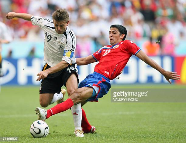 German midfielder Bernd Schneider is challenged by Costa Rican defender Michael Rodriguez during their opening match at Munich's World Cup Stadium in...