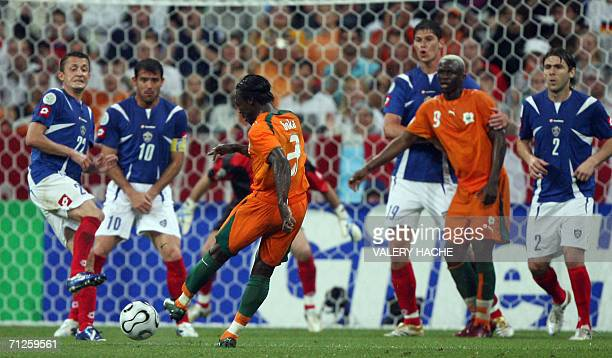 Ivorian defender Arthur Boka takes a shot as Ivory Coast and Serbia and Montenegro players battle for position during the opening round Group C World...
