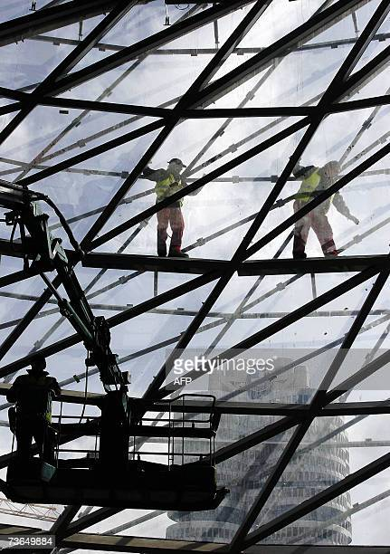 Men work on the facade of the socalled BMW World of German luxury car maker BMW in Munich southern Germany 21 March 2007 The futuristic building by...