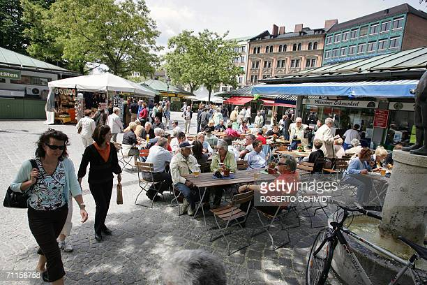 Tourists and locals alike sit out in a beer garden in the Viktualienmarkt area of downtown Munich 08 June 2006 one day ahead of the city's hosting of...