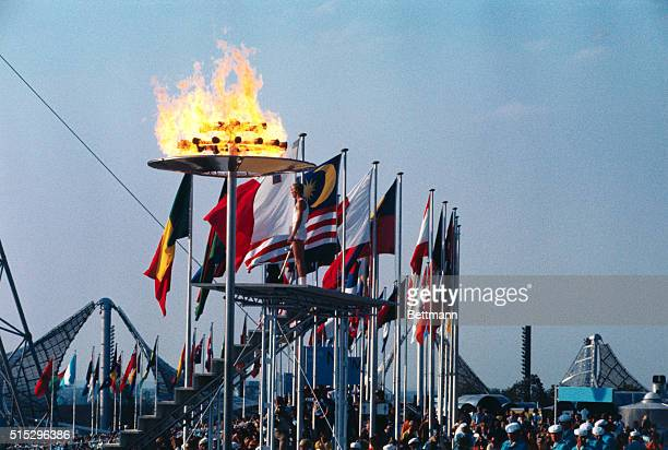 Munich Germany With a backdrop of flags and a roaring flame overhead Gunter Zahn pauses after lighting the Olympic flames signifying the opening of...