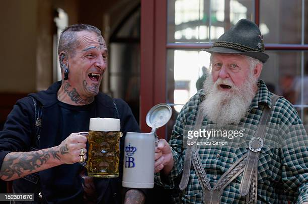 Munich inhabitants one with a Maori style tattoo the other dressed in traditional Bavarian Lederhosen trousers cheer with beer steins three days...