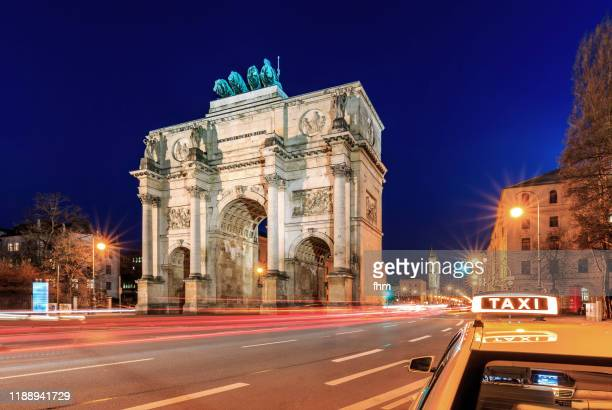 munich siegestor at blue hour wth taxi-sign (bavaria, germany) - local landmark stock pictures, royalty-free photos & images