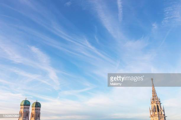 munich skyline against blue summer sky. copy space. towers of the old town hall and frauenkirche. - marienplatz stockfoto's en -beelden