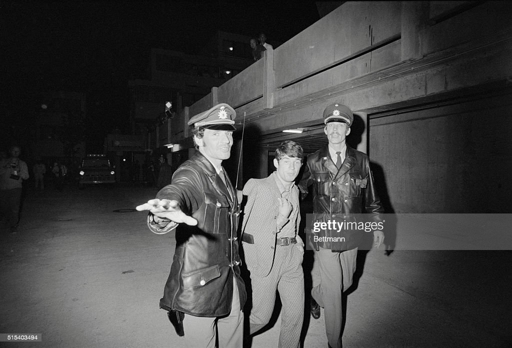 Two Munich policemen ward off a photographer as they escort an unidentified prisoner away from the Israeli team quarters at the Olympic Village here late September 5, following the departure of a group of Arab guerrillas and the Israeli Olympians they were holding hostage.