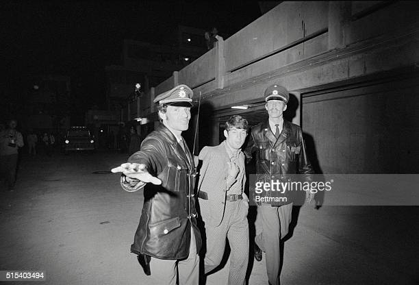Two Munich policemen ward off a photographer as they escort an unidentified prisoner away from the Israeli team quarters at the Olympic Village here...