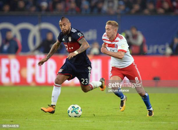 Munich's Arturo Vidal and Hamburg's Lewis Holtby vie for the ball during the German Bundesliga soccer match between Hamburger SV and Bayern Munich in...