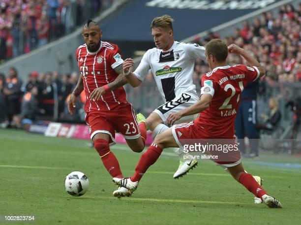 Munich's Arturo Vidal and Philipp Lahm attempt to close down Freiburg's Maximilian Philipp during the German Bundesliga soccer match between Bayern...