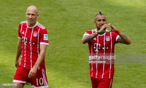 Munich's Arturo Vidal celebrates with teammate Arjen Robben after giving his side a 20 lead during the German Bundesliga soccer match between Bayern...