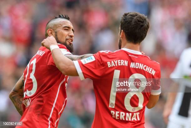 Munich's Arturo Vidal celebrates with teammate Juan Bernat after giving his side a 20 lead during the German Bundesliga soccer match between Bayern...