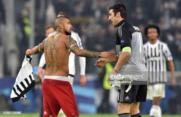 Munich's Arturo Vidal talks to Juve's Gianluigi Buffon after the UEFA Champions League round of 16 first leg soccer match between Juventus Turin and...