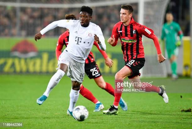 Munich's Canadian midfielder Alphonso Davies vies for the ball with Freiburg's German midfielder Janik Haberer during the German first division...