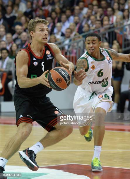 Munich's Heiko Schaffartzik vies for the ball with Athen's AJ Slaughter during the basketball Euroleague group C match between Bayern Munich and...
