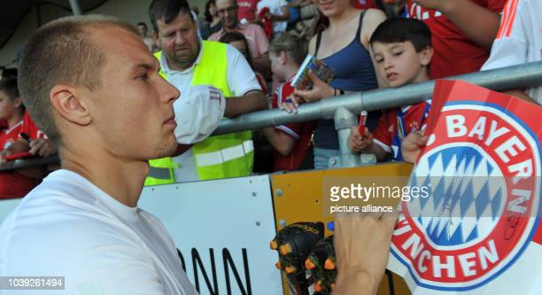 Munich's Holger Badstuber signs an autograph before the tryout match between FC Bayern Munich and an Allgau selection in Memmingen Germany 18 July...