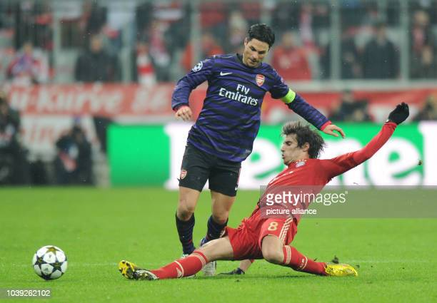 Munich's Javier Martinez and Arsenal's Mikel Arteta vie for the ball during the UEFA Champions League soccer round of sixteen between FC Bayern...