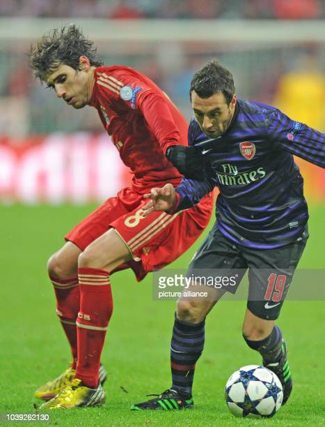 Munich's Javier Martinez and Arsenal's Santi Cazorla vie for the ball during the UEFA Champions League soccer round of sixteen between FC Bayern...