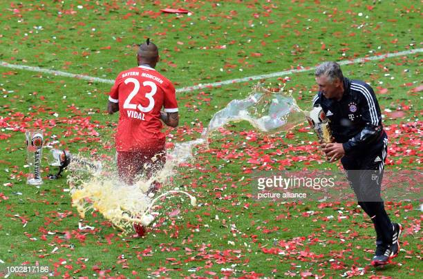Munich's manager Carlo Ancelotti douses Arturo Vidal in beer at the end of the German Bundesliga soccer match between Bayern Munich and SC Freiburg...