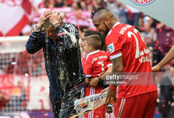 Munich's manager Carlo Ancelotti holds his head after being doused in beer by Arturo Vidal at the end of the German Bundesliga soccer match between...