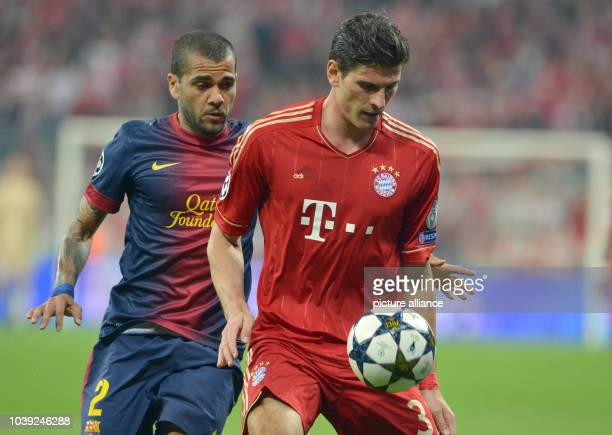 Munich's Mario Gomez and Barcelona's Dani Alves vie for the ball during the UEFA Champions League semi final first leg soccer match between FC Bayern...