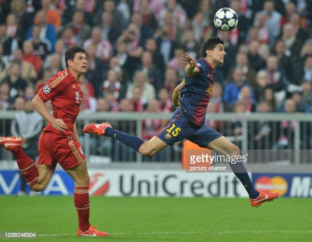 Munich's Mario Gomez and Barcelona's Marc Bartra vie for the ball during the UEFA Champions League semi final first leg soccer match between FC...