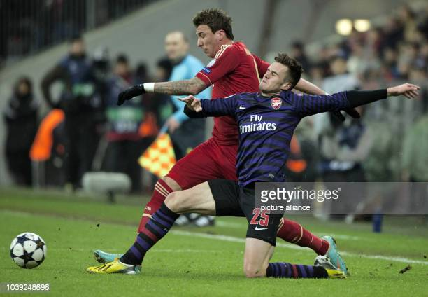 Munich's Mario Mandzukic and Arsenal's Carl Jenkinson vie for the ball during the Champions League round of 16 second leg soccer match between FC...