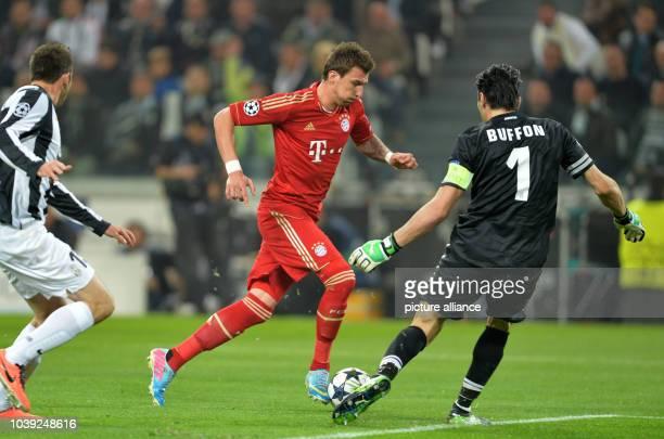 Munich's Mario Mandzukic and Juventus' goalkeeper Gianluigi Buffon vie for the ball during the UEFA Champions League quarter final second leg soccer...