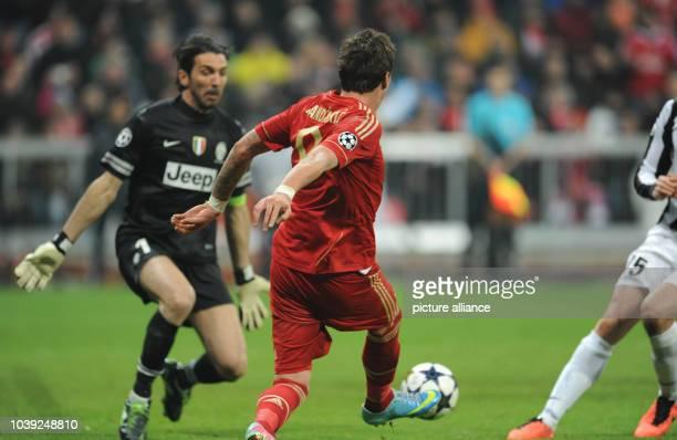 Munich's Mario Mandzukic passes the ball past Turin's goalkeeper Gianluigi Buffon during the UEFA Champions League quarter final first leg soccer...