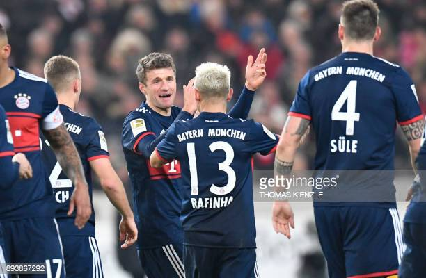 Munich's midfielder Thomas Mueller celebrates with teammates after he scored during the German first division Bundesliga football match between VfB...