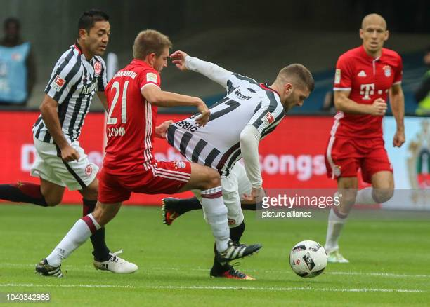 Munich's Phillip Lahm holds the jersey of Ante Rebic of Frankfurt with Munich's Arjen Robben running on the right during the match between Eintracht...