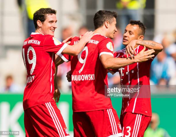 Munich´s Polish forward Robert Lewandowski celebrates after scoring the first goal with midfielder Sebastian Rudy and Brazilian defender Rafinha...