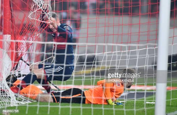 Munich's Polish forward Robert Lewandowski falls down next to Stuttgart's goalkeeper RonRobert Zieler during the German first division Bundesliga...