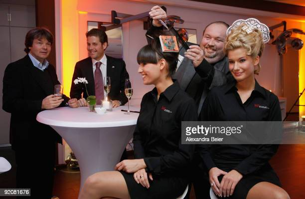 Munich's prominent hairdresser Wolfgang Lippert poses with two models as event manager Philip Greffenius and caterer Michael Kaefer watch them during...
