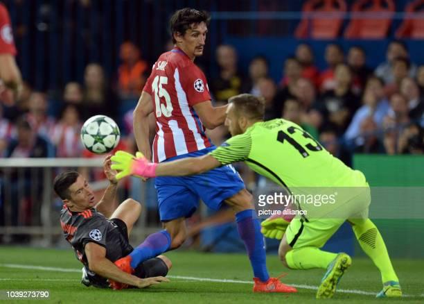 Munich's Robert Lewandowski in action against Madrid's Stefan Savic and goalkeeper Jan Oblak during the Champions League Group D soccer match...
